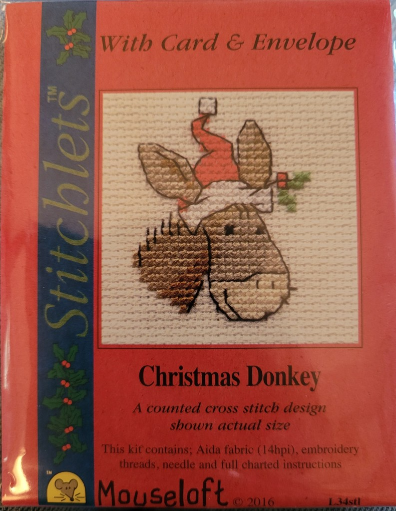 Package with cross stitched donkey with Santa hat.